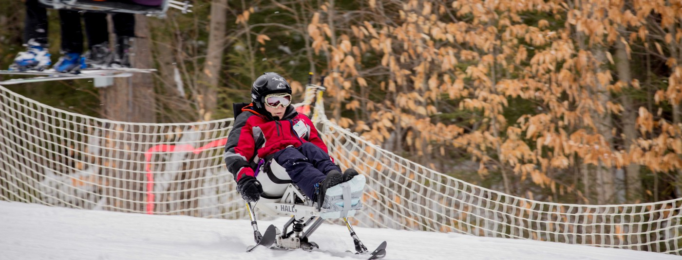 camper using adaptive ski equipment to go down ski slope