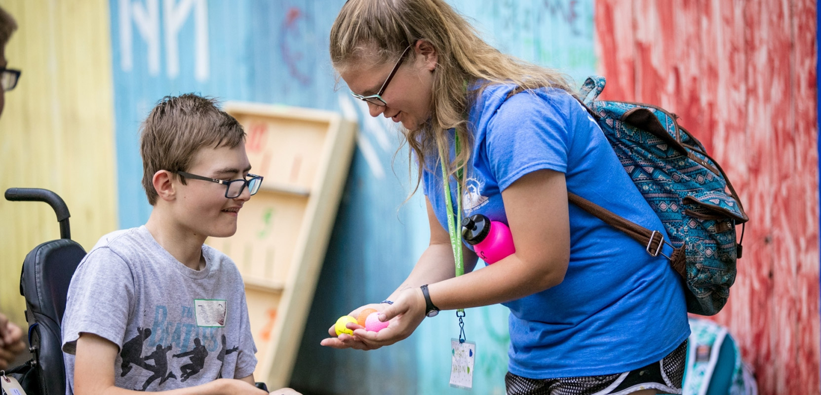 counselor helps camper in wheelchair select his mini golf ball