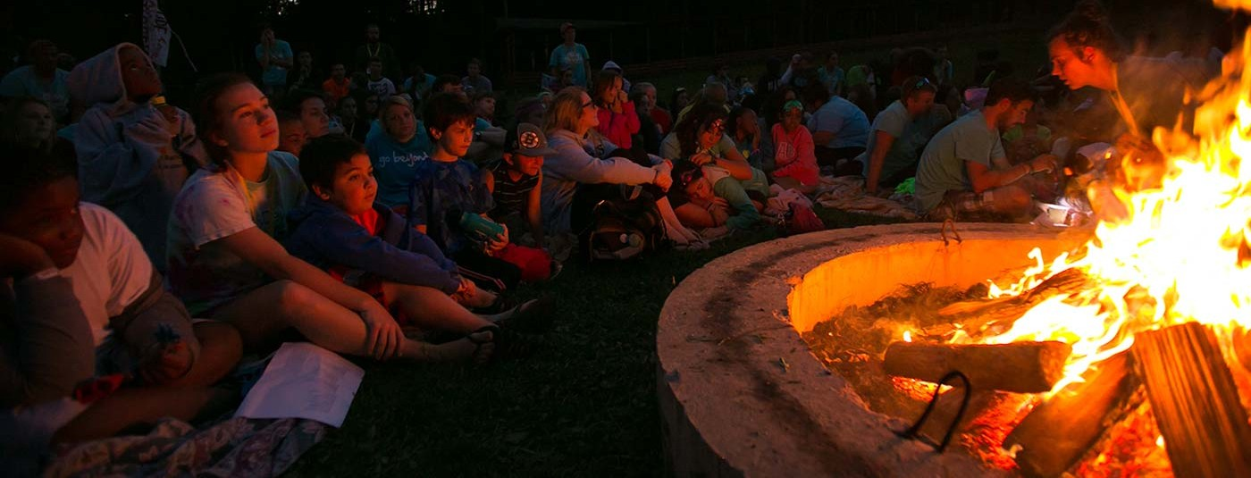 campers and counselors sitting around large fire at night
