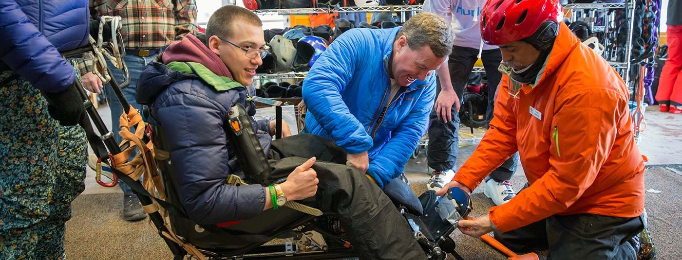 camper being fitted for adaptive ski gear