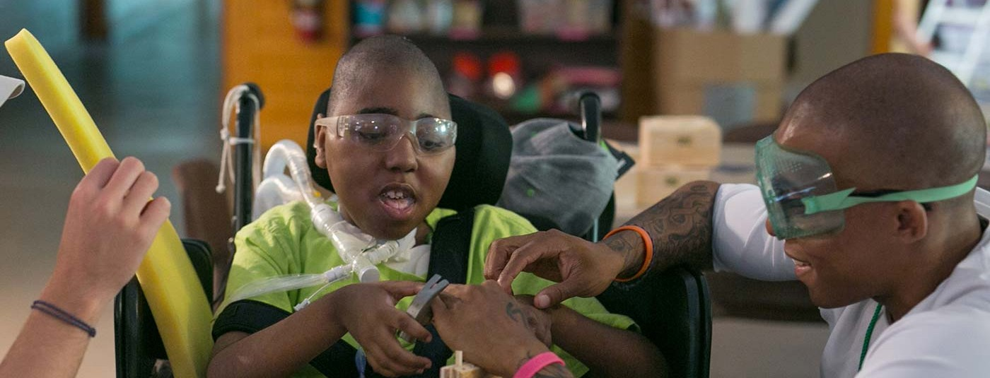 boy in wheelchair being helped perfect his carpentry with counselor