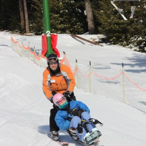 Skier assisting a camper during the Adaptive Winter Sports Program