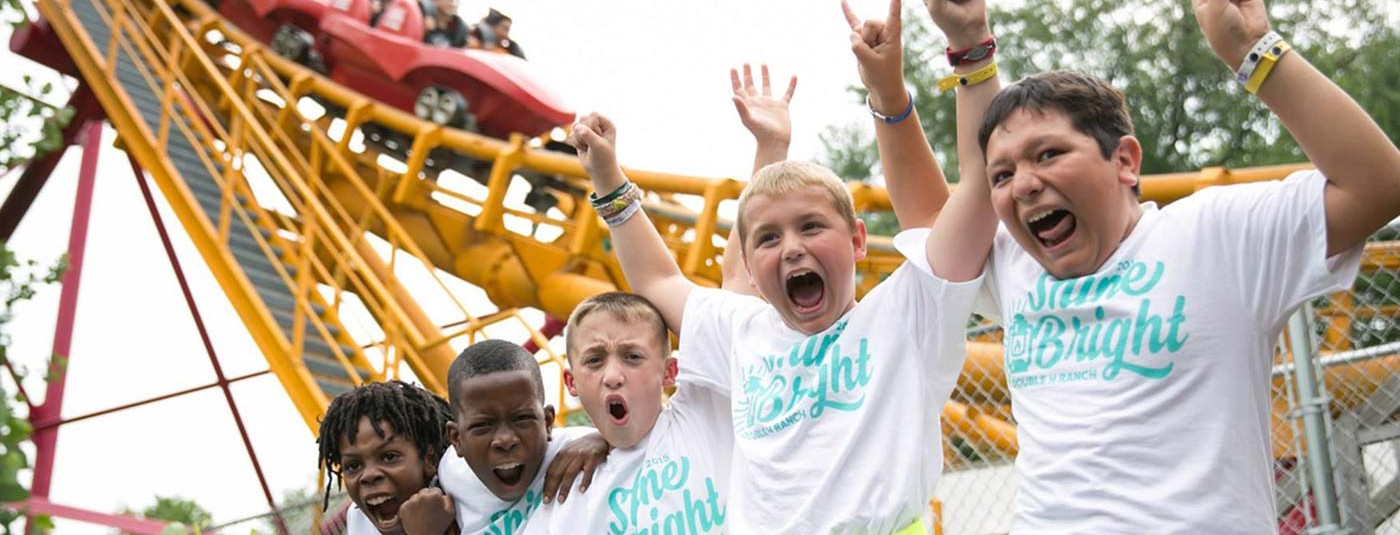 five young boys going crazy in front of roller coaster