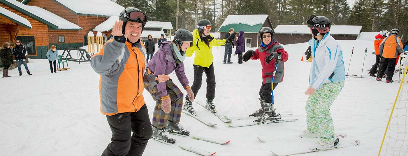 man smiles and waves with group of skiers
