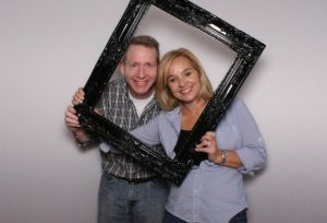 couple holds up picture frame and pose for photo