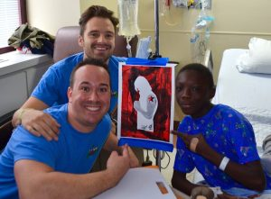 two counselors show off painting with boy in hospital