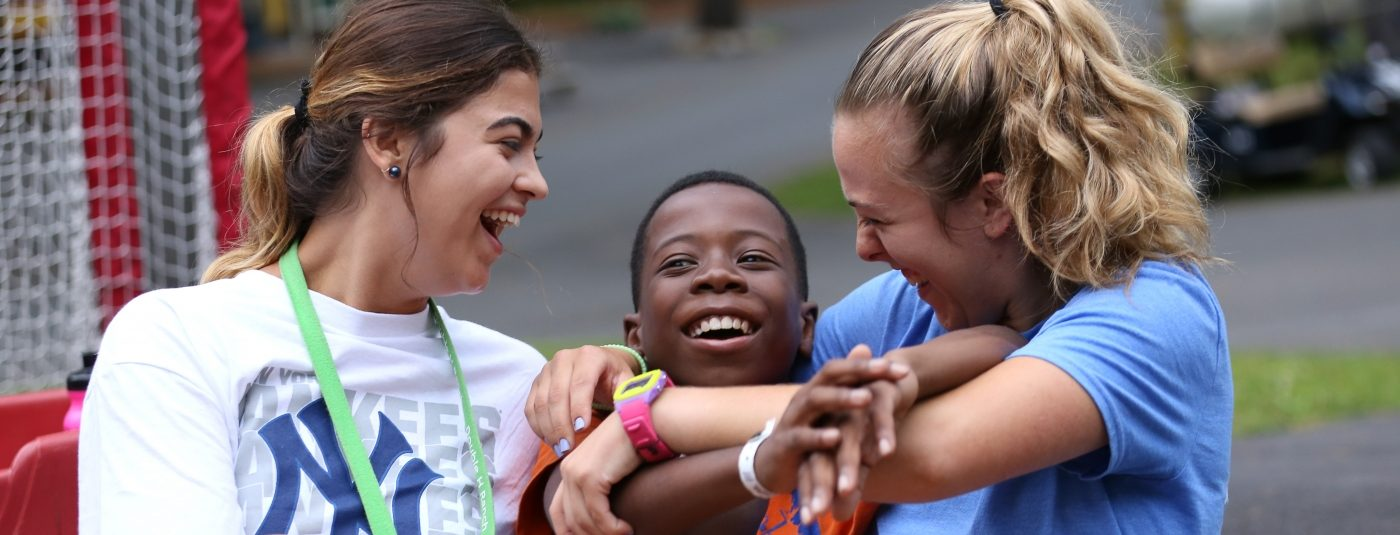 Counselors hugging smiling camper