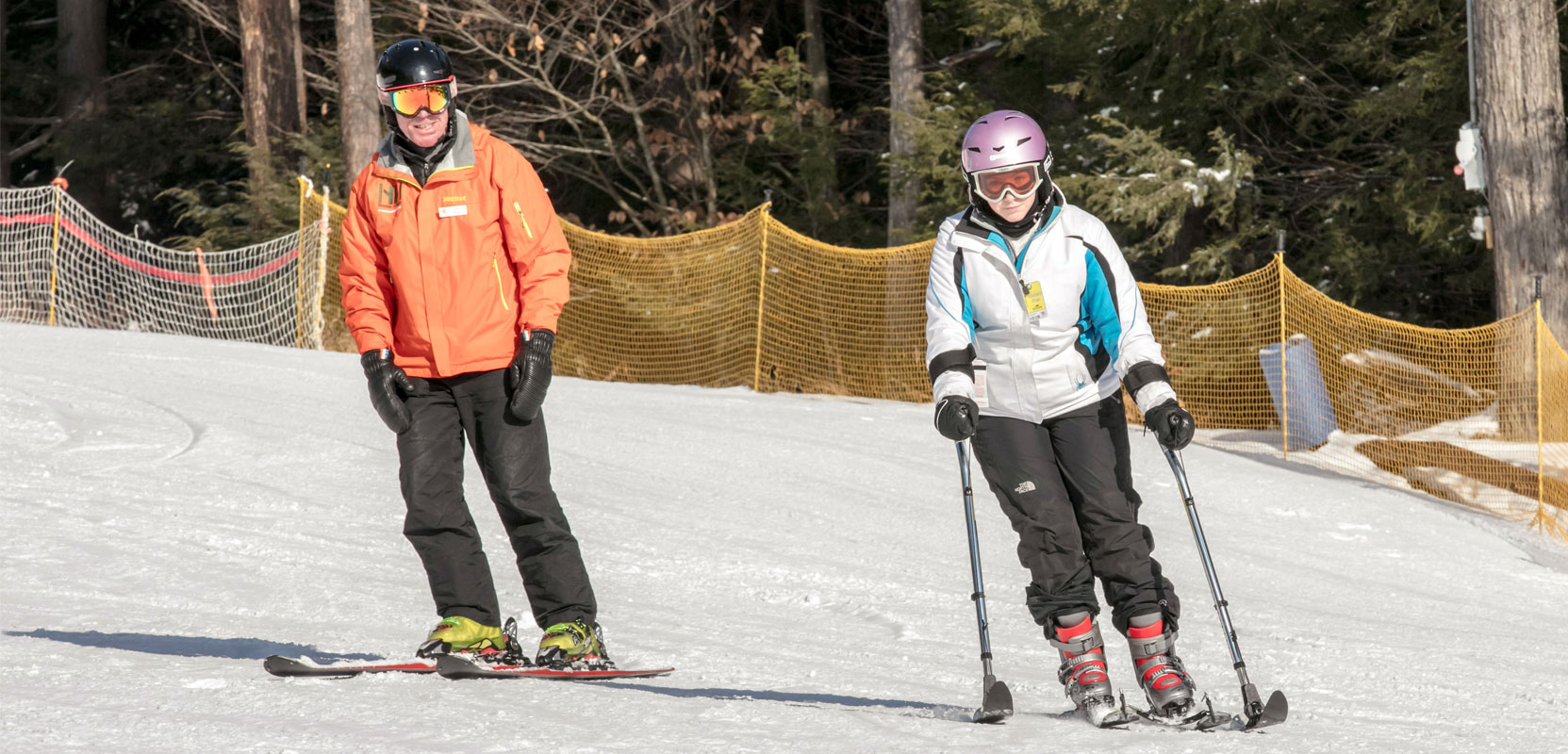 ski instructor and girl using adaptive ski equipment going down the slopes