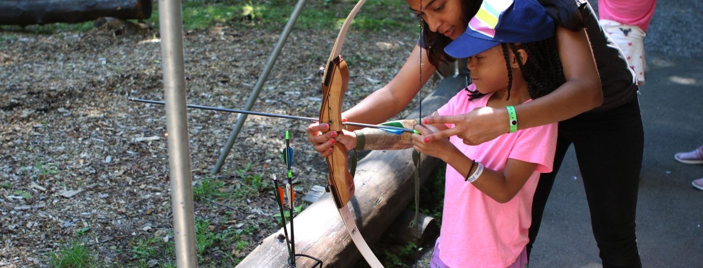 female camper and counselor practicing at archery range