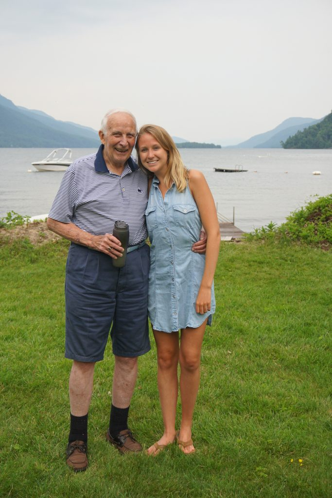 carly robb and grandfather posing in front of lake