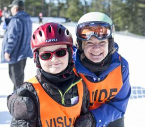 skier and guide smiling on the mountain