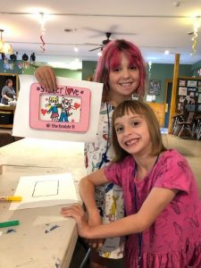 camper sisters showing off art project