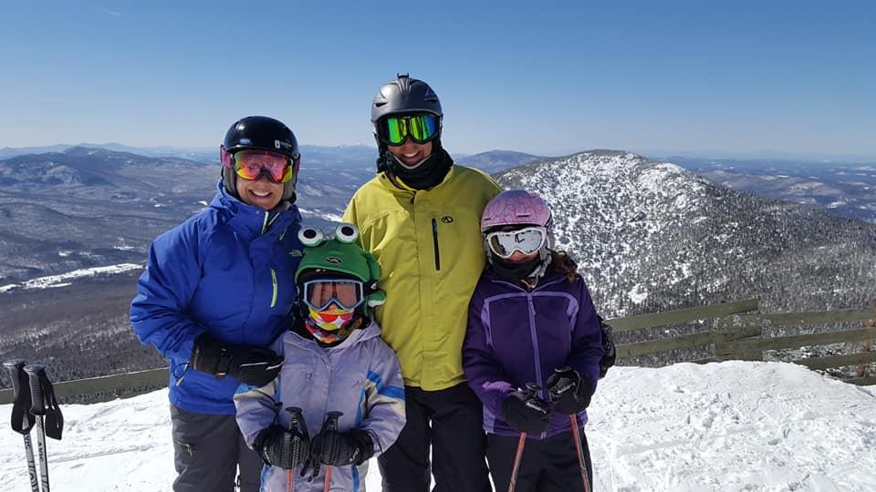 family posing on top of ski mountain