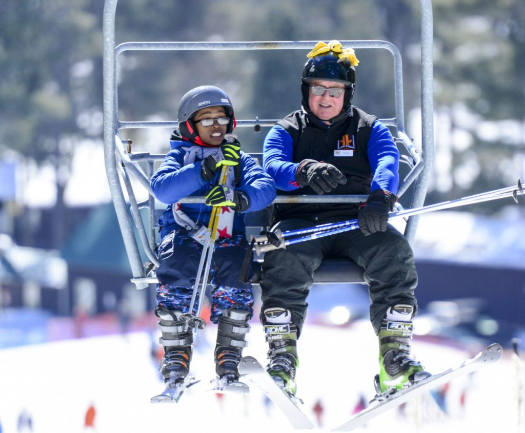 skiers riding on chair lift