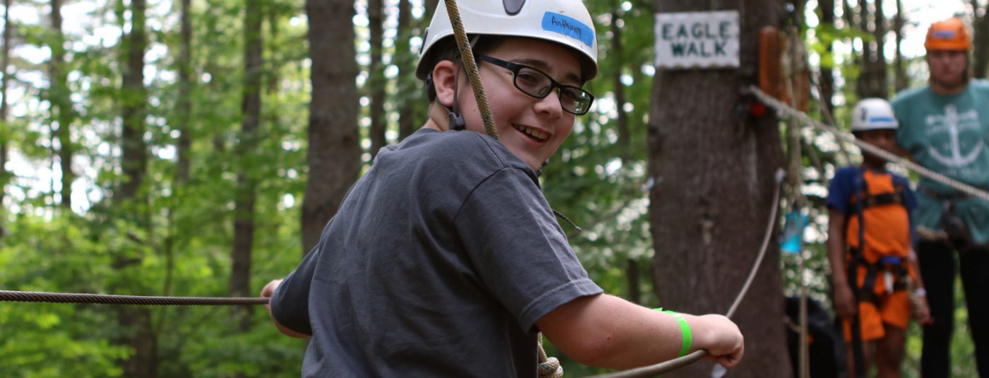 camper wearing helmet looking back on high ropes course