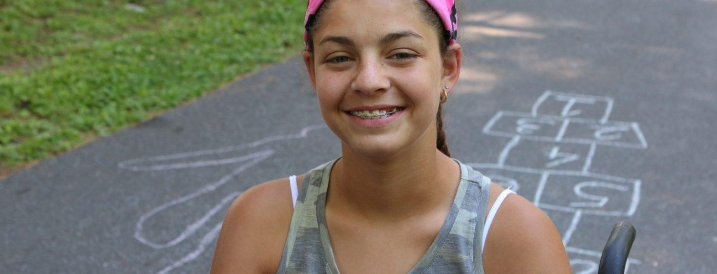 girl with pink headband smiling at camera
